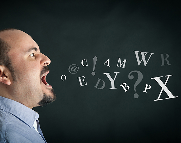 Angry man shouting against black background with letters coming